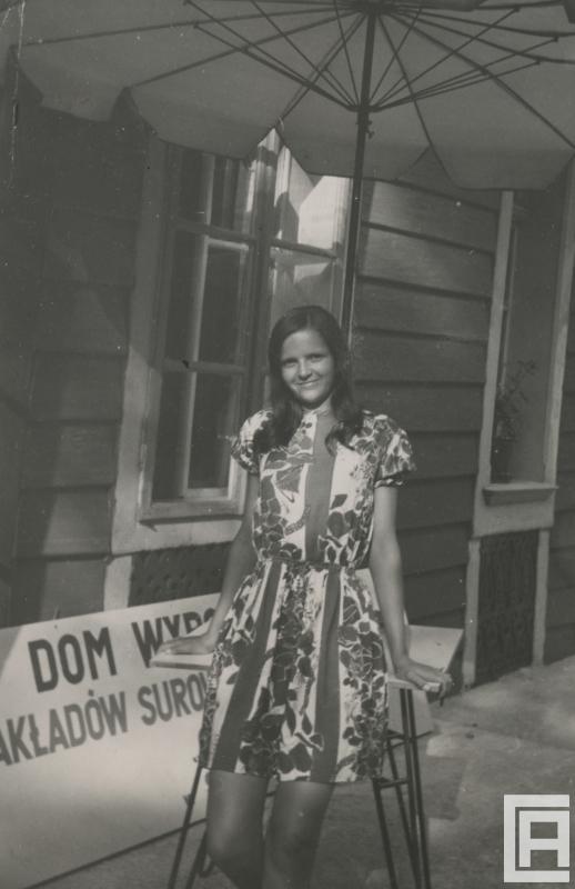 Młoda dziewczyna w kwiecistej sukience pozuje do zdjęcia pod parasolem.