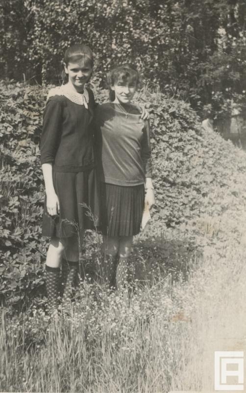 Dwie dziewczynki pozują do zdjęcia wśród zieleni.
