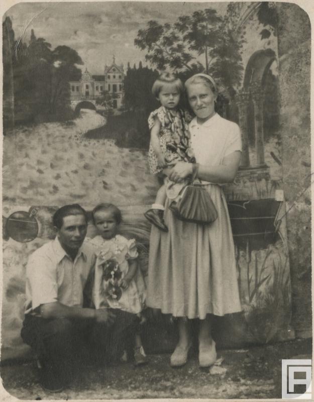 Kobieta i mężczyzna z dwojgiem dzieci pozują do zdjęcia przy odpustowej ściance fotograficznej.