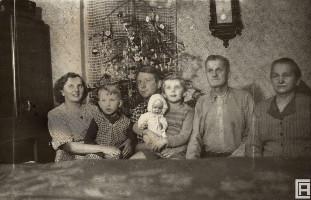 Fotografia rodziny, która siedzi przy stole. Za nimi, w rogu pokoju stoi choinka bożonarodzeniowa.