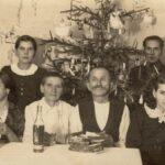 Fotografia przedstawia rodzinę siedzącą przy stole. Z tyłu, za nimi stoi w rogu pokoju, świąteczna choinka.