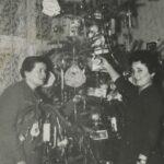 Fotografia świątecznej choinki, z lewej i z prawej strony stoją kobiety.