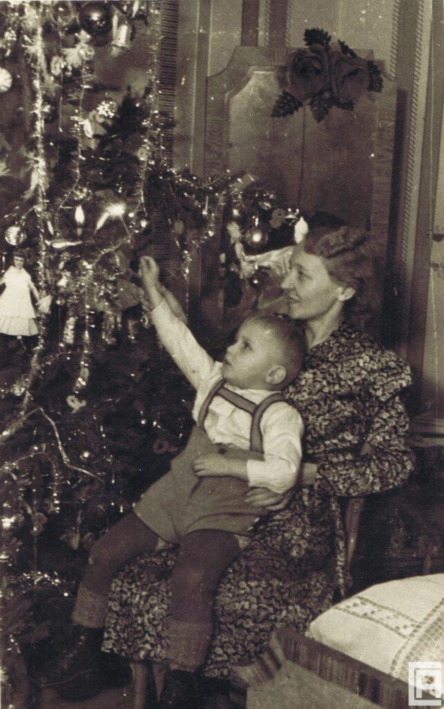 Fotografia mamy i dziecka przy świątecznej choince. Mama siedzi na krześle i na kolanach trzyma dziecko, które dotyka choinki.