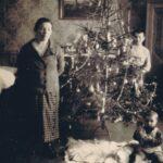 Fotografia przedstawiająca choinkę. Obok choinki po lewej stronie stoi kobieta, po prawej stoi chłopiec i siedzi dziecko.