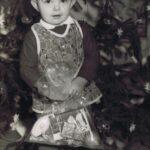 Fotografia chłopczyka z prezentem na tle choinki.