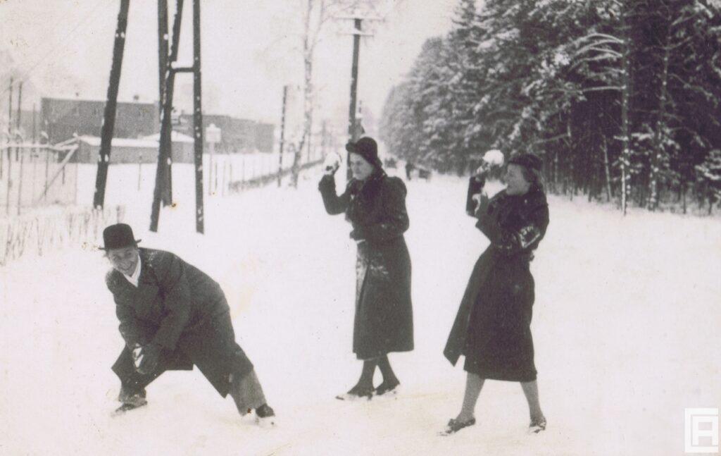 Fotografia przedstawia 2 kobiety i mężczyznę, którzy rzucają w siebie śnieżkami.