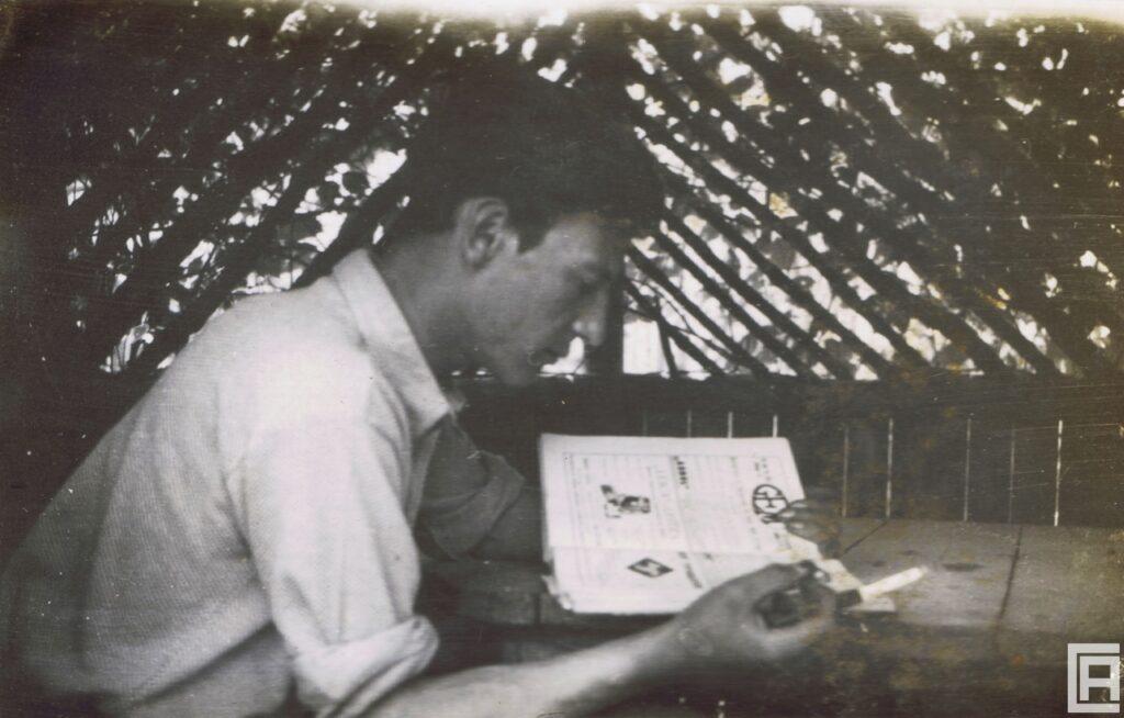 Mężczyzna siedzi i czyta książkę. Zdjęcie zrobione z boku. Widać profil mężczyzny.