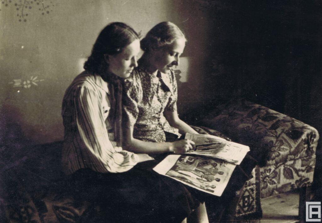 Dwie młode kobiety siedzą na kanapie. Na ich kolanach leży ilustrowana gazeta, którą przeglądają.