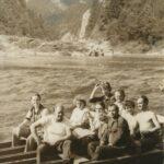 Widoczne dziesięć osób na łódce prowadzonej przez flisaka po Dunajcu. W tle krajobraz.