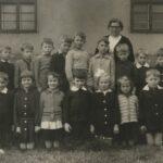 Zdjęcie klasowe przed budynkiem: jedenaścioro dzieci z nauczycielką.