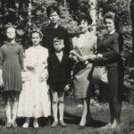 Las. Trzy odświętnie ubrane dorosłe kobiety, obok troje dzieci. Środkowa dziewczynka w stroju komunijnym.