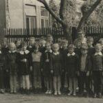 Zdjęcie pod drzewem: dwudziestodwuosobowa klasa z nauczycielką.