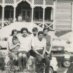 Kobieta, mężczyzna i czworo dzieci pozuje do zdjęcia przy samochodzie. Z tyłu dom wypoczynkowy.