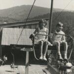 Dwoje dzieci na krzesełku wyciągowym. W dole widoczni ludzie czekający w kolejce do wjazdu. Panorama gór.