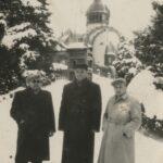 Trzech mężczyzn w zimowej odzieży pozuje do zdjęcia na zaśnieżonym pagórku.