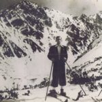 Mężczyzna pozuje do zdjęcia na nartach, w tle masyw górski.