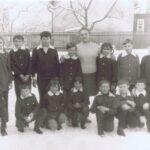 Grupa 15 dzieci w mundurkach pozuje do zdjęcia z nauczycielką na zaśnieżonym podwórzu.