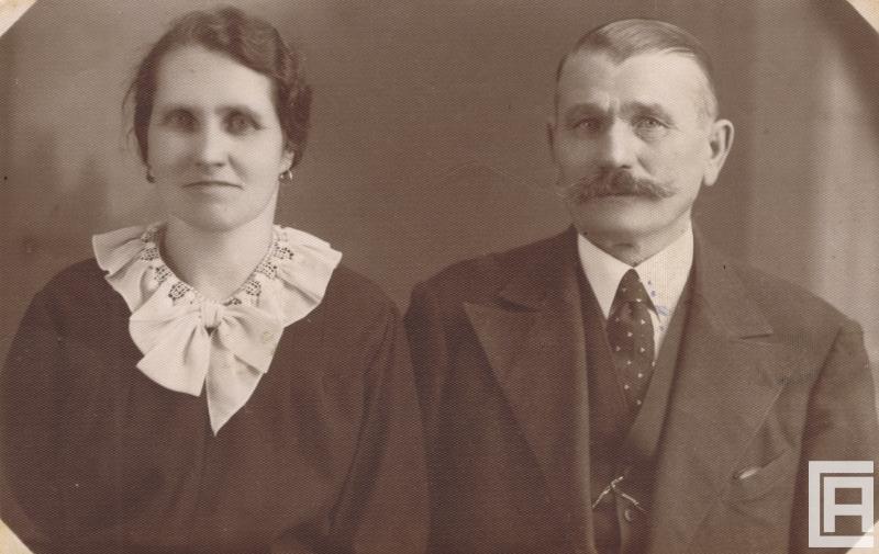 Zdjęcie portretowe kobiety ubranej odświętnie, obok mężczyzna z wąsami, w garniturze.