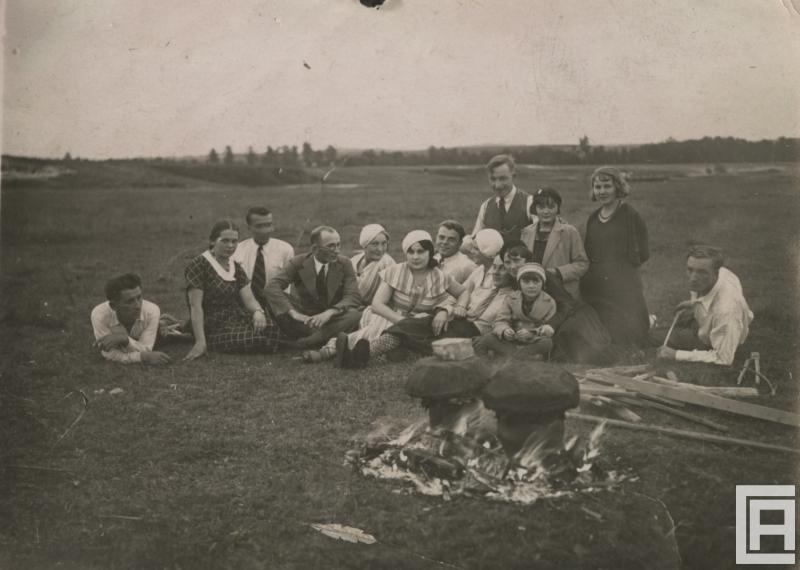 Grupa osób pozuje siedząc na trawie. Przed nimi ognisko i dwa garnki pieczonych ziemniaków. Garnki są przykryte darniem.