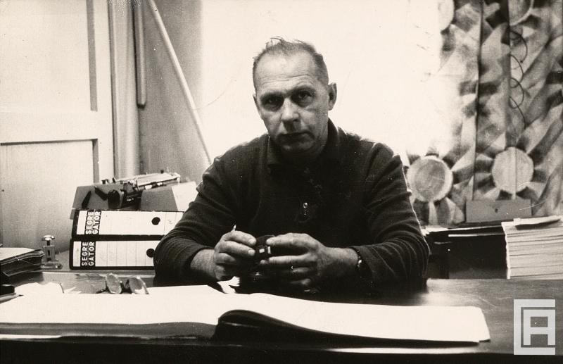 Mężczyzna siedzi przy biurku. Za nim widoczna maszyna do pisania, segregatory, dokumenty. Na blacie leży aparat, okulary, otwarta książka.