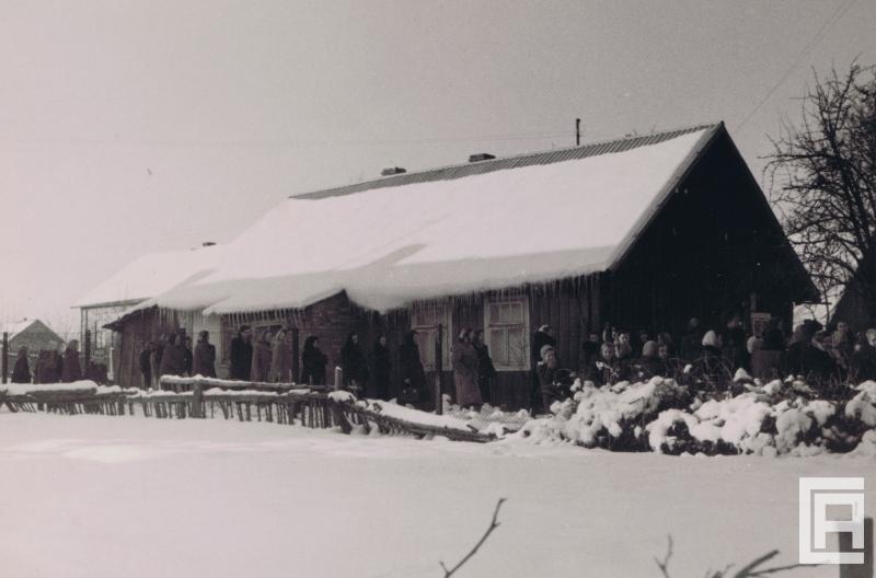 Przed chata pokrytą śniegiem, ze zwisającymi z dachu soplami, ustawiła się kolejka ludzi: mężczyzn, kobiet i dzieci.