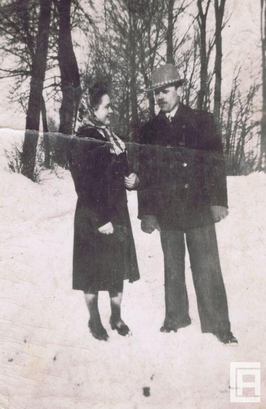 Kobieta i mężczyzna w odświętnych strojach pozują do zdjęcia na zaśnieżonym zboczu.