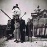 Osiem osób pozuje do zdjęcia z bałwanem wyższym od dorosłego człowieka. W tle płot i zabudowania.