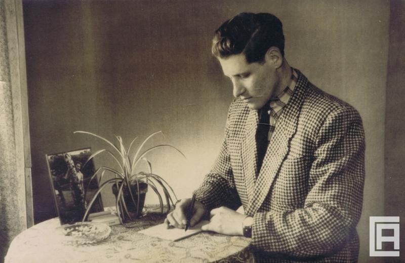 Mężczyzna zapisuje coś przy stoliku. Na blacie postawiono popielniczkę, roślinę doniczkową - zielistkę, zdjęcie kobiety w ramce.