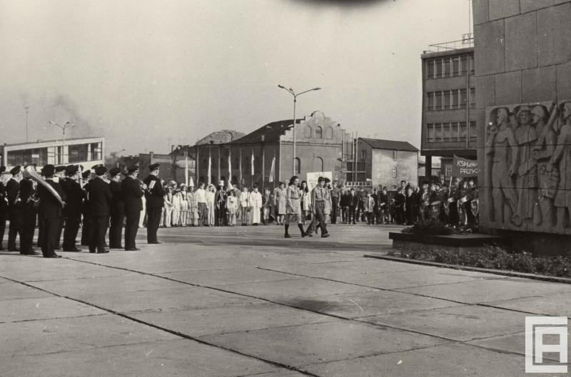 Wokół placu zebrana jest grupa ludzi: orkiestra zakładowa, osoby w kostiumach. Dwoje harcerzy idzie w kierunku pomnika z kwiatami. W tle widoczny jest budynek synagogi.