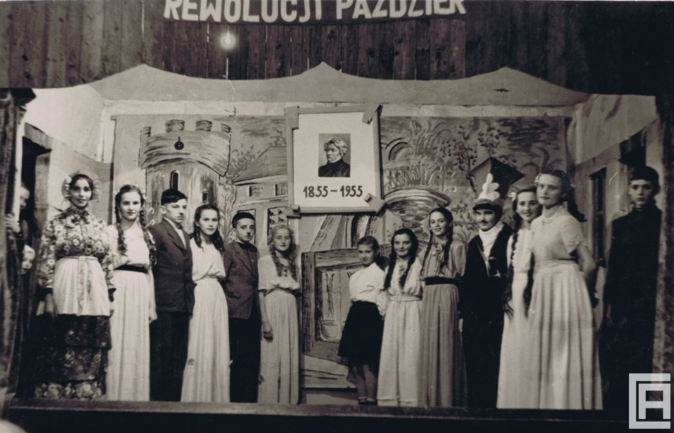 Grupa aktorów - uczniów szkoły podstawowej stoi na scenie Domu Ludowego w Płazie. Nad nimi wisi portret Adama Mickiewicza.