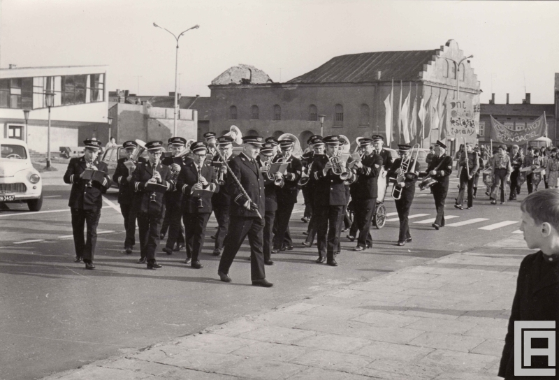 Pochód ludzi, na czele orkiestra w mundurach. Z tyłu widoczna synagoga.