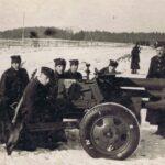 Siedmiu żołnierzy pozuje do zdjęcia z działem artyleryjskim. W tle widoczne pole, las, inni żołnierze.