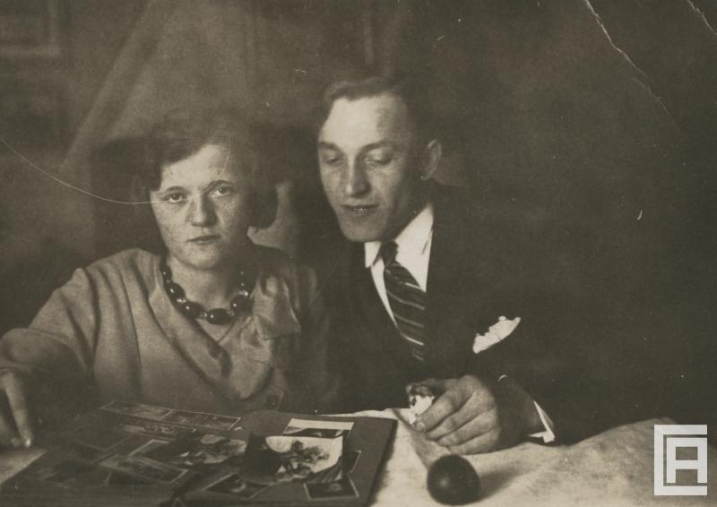 Dwoje ludzi siedzi przy stole, na którym leży otwarty album fotograficzny. Kobieta patrzy w obiektyw, ma na szyi korale. Mężczyzna w garniturze spogląda na zdjęcia, trzyma nadgryzione jabłko.
