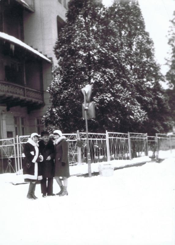 Mężczyzna pozuje do zdjęcia z dwoma kobietami u boku w strojach wykończonych białych futrem.