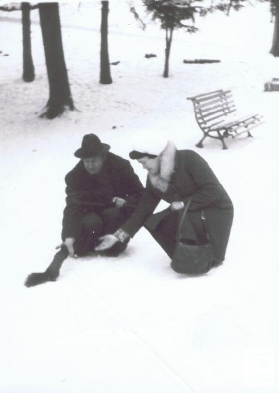 Kobieta i mężczyzna w zaśnieżonym parku klęczą z wyciągniętymi dłońmi, podchodzi do nich wiewiórka.