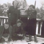 Sześć kobiet stoi przy ośnieżonej balustradzie. Dwie z nich pochylają się i lepią śnieżki.