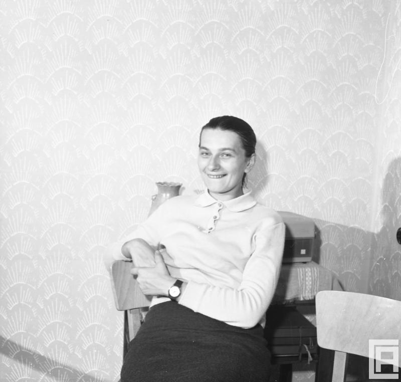 Uśmiechnięta kobieta siedzi na krześle.