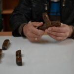 Mężczyzna składa zabawkę, dopasowuje element 1 i 2.