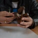 Mężczyzna składa zabawkę, dopasowuje element 1-4, dokłada 5.