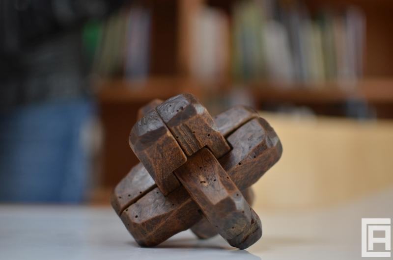Drewniana zabawka na stole, w tle widoczne regały z książkami