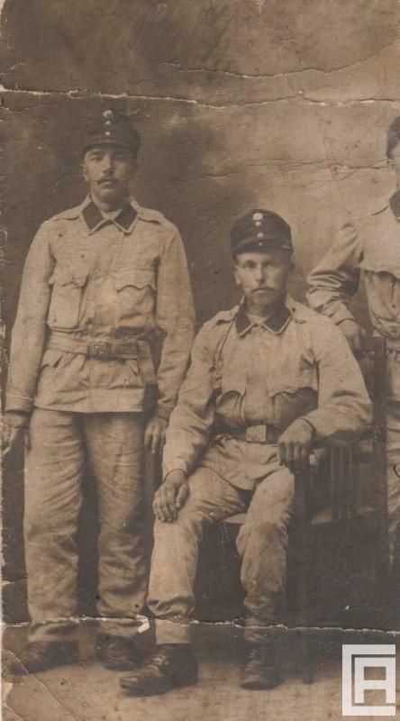 Trzech mężczyzn w mundurach armii Austro-Węgier, środkowy siedzi na krześle. Ostatni jest widoczny tylko w połowie.