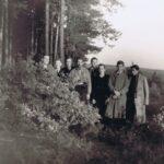 Osiem osób pozuje do zdjęcia na skraju lasu.