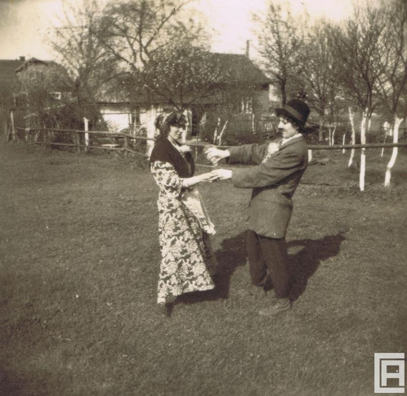 Dwie kobiety w przebraniach karnawałowych tańczą w ogrodzie.