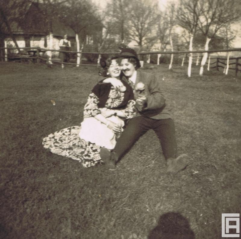 Dwie kobiety w przebraniach karnawałowych siedzą na trawie.
