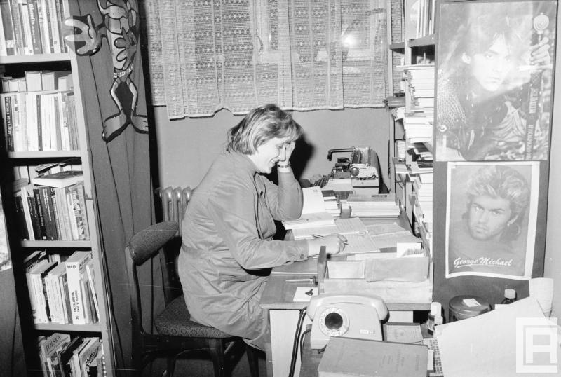 Wnętrze biblioteki, przy stole siedzi bibliotekarka. Widoczne książki, telefon, maszyna do pisania, dokumenty, plakaty.