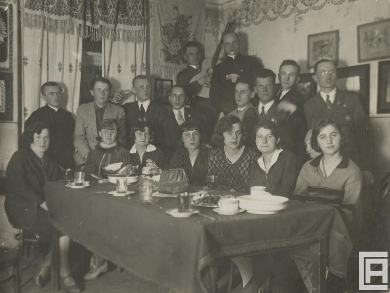 Siedemnaście osób jest ustawionych wokół zastawionego stołu, w tym trzech duchownych.