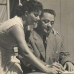 Fotografia przedstawia scenę, biuro. Mężczyzna siedzi przy biurku i pisze, kobieta pochyla się nad nim i pokazuje coś na kartce. Stroje współczesne.