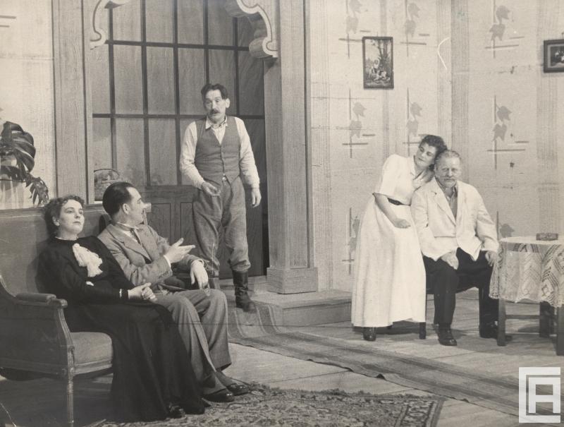 Fotografia przedstawia scenę, salonik. Kobieta z mężczyzną siedzą na kanapie, naprzeciw inna para przy krześle, do pomieszczenia wszedł trzeci mężczyzna. Stroje XIX-wieczne.