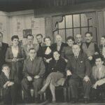 Fotografia przedstawia scenę, salonik. Zdjęcie grupowe obsady w strojach XIX-wiecznych. Jeden rząd stoi, drugi siedzi: 12 mężczyzn, 5 kobiet.