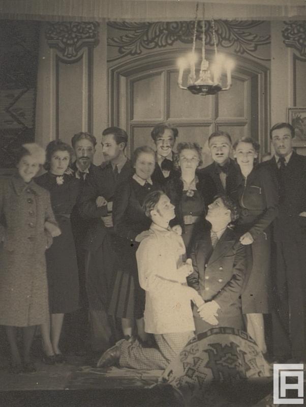 Fotografia przedstawia scenę, pod żyrandolem. Zdjęcie grupowe w kostiumach z początku XX wieku. Przed grupą aktorów klęczą dwie osoby.